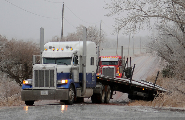 A semi-truck driver's trailer slips off the pavement on Wheat Capital Road as sleet continued to fall in Garfield County Saturday, Dec. 21, 2013. (Staff Photo by BONNIE VCULEK)