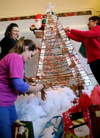 Galin Edmonds, Chaunna Spears and Diana Cox (from left) decorate an eight-foot aluminum with Christmas decorations before a special meeting at the former Harrison Elementary School Thursday, Dec. 12, 2013. (Staff Photo by BONNIE VCULEK)