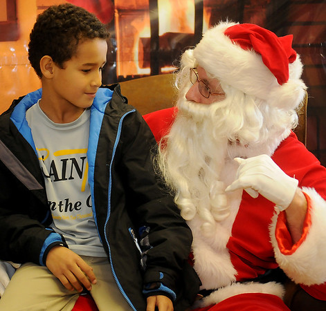 Jaxyn Ward visits with Santa during the Central National Bank open house Friday, Dec. 6, 2013. Ward and other 3rd-5th grade students from St. Joseph Catholic Church sang Christmas carols for the bank's guests. (Staff Photo by BONNIE VCULEK)