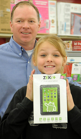 "Jazmyn Koehn smiles as she holds the new ZEKI tablet Capt. Bryan Skaggs helped her pick out during Koehn's ""Shop with a Cop"" at the Big K Mart Saturday, Dec. 14, 2013. Sixty-five children were able to spend $100 each because of the generosity of the Enid Police Department and the Oklahoma Highway Patrol Troop J officers. (Staff Photo by BONNIE VCULEK)"