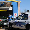 An Aqua Express employee scrubs a dirty vehicle as an Enid Police Department Patrolman waits in line for a car wash Saturday, Dec. 28, 2013. As temperatures reached the upper 50s-60s, drivers cleaned their vehicles, before freezing temperatures return Sunday. (Staff Photo by BONNIE VCULEK)