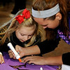 Ella Branstetter creates a Christmas ornament with the help of a March of Dimes volunteer during Breakfast with Santa at Enid High School Saturday, Dec. 7, 2013. (Staff Photo by BONNIE VCULEK)