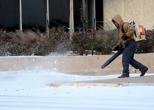 A gentleman uses a gasoline powered blower to remove ice from the sidewalks outside Central National Bank Friday, Dec. 6, 2013. The winter storm that moved across Enid and Garfield County brought a wintery mix of sleet and light snow late Thursday into Friday morning. (Staff Photo by BONNIE VCULEK)