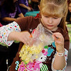 Avrey Ransom, 7, shakes popcorn into a glove as she enjoys the different craft projects during the 15th annual March of Dimes Breakfast with Santa at Enid High School Saturday, Dec. 7, 2013. (Staff Photo by BONNIE VCULEK)