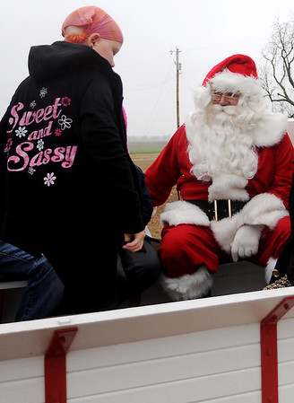 Santa greets one of the children during wagon rides at Bennie's Barn open house Sunday, Dec. 21, 2014. Bennie's Barn, Inc. heals hearts and hooves through horse therapy at 4914 E. Rupe. Horseback riding classes, lessons and therapy activities will begin in February. (Staff Photo by BONNIE VCULEK)