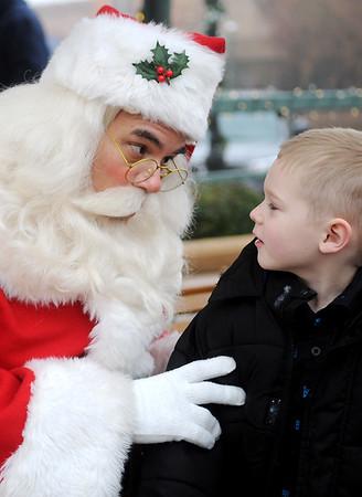 Santa shares a secret with Tristen Ennis during Candy Cane Cash in downtown Enid Saturday, Dec. 13, 2014. (Staff Photo by BONNIE VCULEK)
