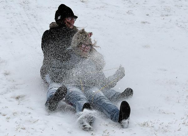 Kelly and Tara Lee are sprayed with sleet while sledding on the north Van Buren overpass Sunday December 27, 2015. (Billy Hefton / Enid News & Eagle)