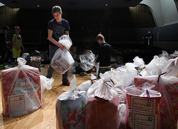 Waller Middle School seventh grader, Hayden Johnson, stacks bags of gifts Friday December 16, 2016 as part of the Waller Gives To Others program. (Billy Hefton / Enid News & Eagle)
