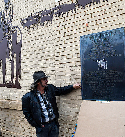 """Artist Paul Stone helps to unveil a plaque for his metal mural """"The Trail"""" following a ribbon cutting and dedication ceremony Thursday December 15, 2016 in downtown Enid. (Billy Hefton / Enid News & Eagle)"""