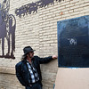 "Artist Paul Stone helps to unveil a plaque for his metal mural ""The Trail"" following a ribbon cutting and dedication ceremony Thursday December 15, 2016 in downtown Enid. (Billy Hefton / Enid News & Eagle)"
