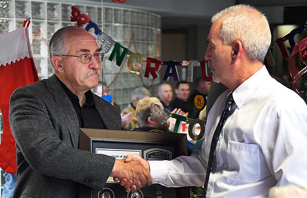 Capt.Tom Nichols (left) shakes hands with Chief Brian O'Rourke during a retirement cememony Wednesday December 21, 2016 at the Enid Police Department. (Billy Hefton / Enid News & Eagle)