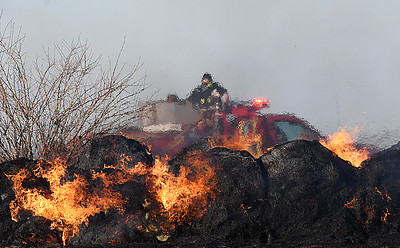 A unit from a rual fire department drives pass burning hay bales in a field on south 126th street near Fairmont Thursday December 29, 2016 after the bales were caught on fire by a grass fire. Units from multiple rural fire departments responded to the fire. (Billy Hefton / Enid News & Eagle)