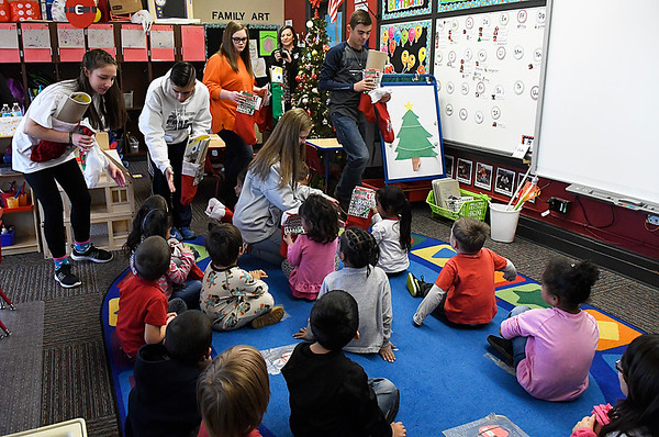 Waller Middle School students, Kylee Mears, Garrett Brooks, Alyssa Wall, Kynlee Skaggs and Ruben Daniels, hand out Christmas stockings to students at Carver Early Childhood Center as part of Waller Gives to Others program Monday December 19, 2016. (Billy Hefton / Enid News & Eagle)