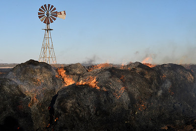 Round bales of hay burn in a field on south 126th street near Fairmont Thursday December 29, 2016 after being caught on fire by a grass fire. Units from multiple rural fire departments responded to the grass fire. (Billy Hefton / Enid News & Eagle)