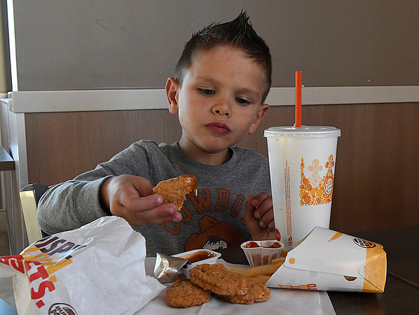 Jase Dershem dips a nugget in sauce while eating at Burger King Thursday December 1, 2016. (Billy Hefton / Enid News & Eagle)