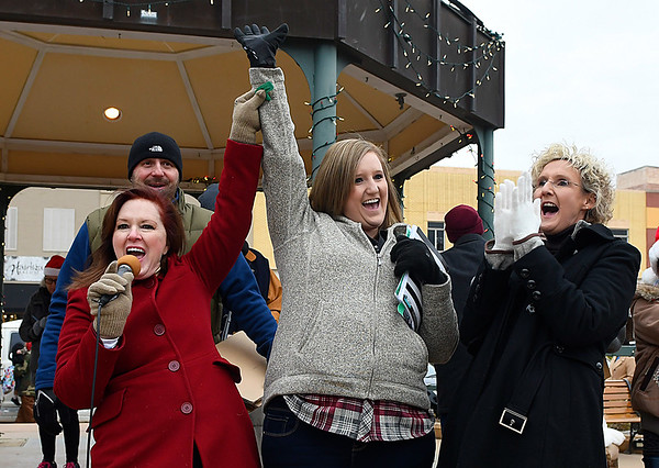 Karyssa Franklin (center) celebrates with her mother, Linda Childress (right) after April Danahy (left) confirms the $7500 winning ticket in the Candy Cane Cash drawing Saturday December 10, 2016 on the Garfield County Courthouse lawn. (Billy Hefton / Enid News & Eagle)