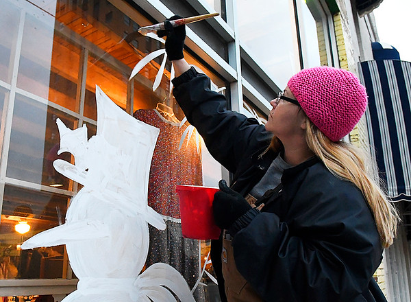 Christy Timberlake paints a winter scene on window of Broadway Antiques in downtown Enid MOnday December 12, 2016. (Billy Hefton / Enid News & Eagle)