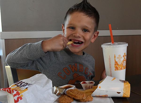 Jase Dershem smiles while eating a french fry at Burger King Thursday December 1, 2016. (Billy Hefton / Enid News & Eagle)