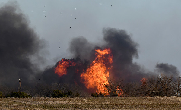 Debris fills the air as a fire burns near the intersection of Fox Road and 174th street Friday December 30, 2016. (Billy Hefton / Enid News & Eagle)