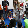 Waller Middle School students, Kylee Mears and Garrett Brooks, hand out Christmas stockings to students at Carver Early Childhood Center as part of Waller Gives to Others program Monday December 19, 2016. (Billy Hefton / Enid News & Eagle)