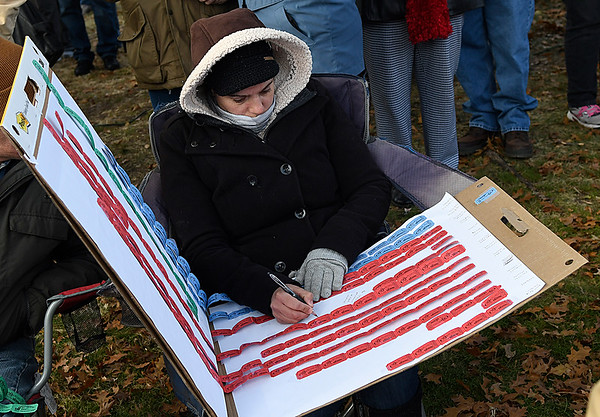Sabine Deshazo searches for the winning ticket in the Candy Cane Cash drawing Saturday December 10, 2016 on the Garfield County Courthouse lawn. (Billy Hefton / Enid News & Eagle)