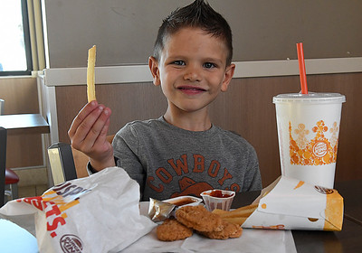 Jase Dershem holds up a french fry while eating at Burger King Thursday December 1, 2016. (Billy Hefton / Enid News & Eagle)