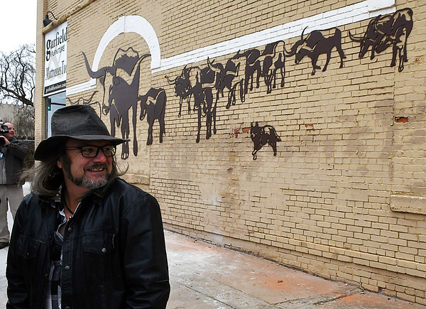 "Artist Paul Stone stands in front of his metal mural ""The Trail"" following a ribbon cutting and dedication ceremony Thursday December 15, 2016 in downtown Enid. (Billy Hefton / Enid News & Eagle)"