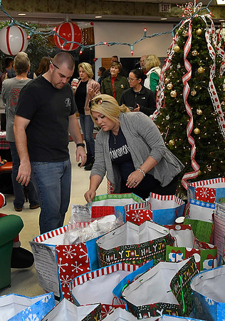 Christy Baker and Pete Talley sort through bags of Christmas gifts to be delivered through RSVP's Santa for Seniors program Thursday December 21, 2017. (Billy Hefton / Enid News & Eagle)