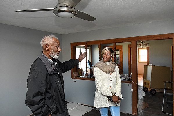 D'Andria Bradford looks on as her father, Joe Bradford, gestures as he describes the damage a house fire caused to his home during an interview. (Billy Hefton / Enid News & Eagle)