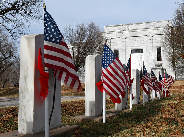 American flags with red ribbons on the graves of veterans at Enid Cemetery Monday December 4, 2017. (Billy Hefton / Enid News & Eagle)