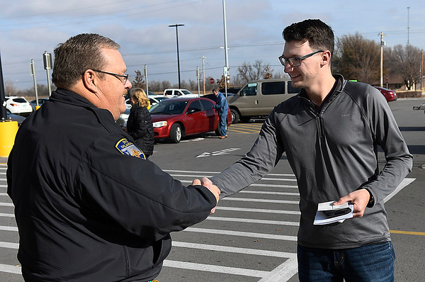 Enid police officer Mike Atchley shakes hands with Timothy Stine after being presenting him with cash from an anonymous donation. (Billy Hefton / Enid News & Eagle)