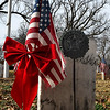 An American flag with red ribbon on the graves of a veteran at Enid Cemetery Monday December 4, 2017. (Billy Hefton / Enid News & Eagle)