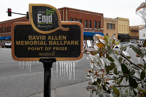 Ice covers the shrub and Main Street Enid sign on the corner of Broadway and Grand Friday December 22, 2017. (Billy Hefton / Enid News & Eagle)