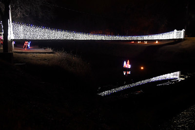 Lights from the bridge at Kingfisher Winter Nights reflect on the water of Uncle John Creek Monday December 3, 2018. The light display runs through December 24, opening at 6 p.m. each night. (Billy Hefton / Enid News & Eagle)