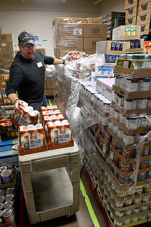 Justin Jones, Warehouse and Facilities Manager at Loaves and Fishes, sorts through a shipment of donates food Monday, December 2, 2019.  (Billy Hefton / Enid News & Eagle)