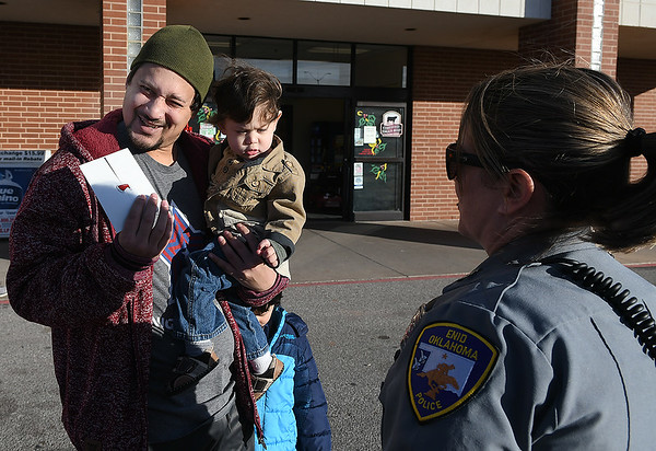 Ismael Bueno with sons, Michael and Gio, smile after getting a cash gift Enid police officers, Nicole Binckley and Brian Hatfield, Thursday, December 19, 2019 at Jumbo's East. The police department is handing out donated money to random people over the next few days. (Billy Hefton / Enid News & Eagle)