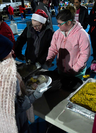 Keely Bibbee (left) and Serah Watson serve food during Christmas Outreach put on by Forgotten Ministries, Your Family Church, Enid Mennonite Brethren Church and local donors Tuesday, December 17, 2019 at Don Haskins Park. (Billy Hefton / Enid News & Eagle)