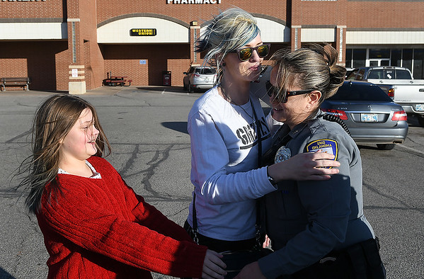 Enid police officer Nicole Binckley gets a hug from Samantha Bode and her daughter, Fisher Young, after the officer gave her a cash gift Thursday, December 19, 2019 at Jumbo's East. The police department is handing out donated money to random people over the next few days. (Billy Hefton / Enid News & Eagle)