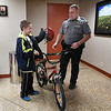 Enid police officer Tom Rhyne presents Justin Bryant with a new bike and helmet Thursday, December 26, 2019 at the Enid Police Station. (Billy Hefton / Enid News & Eagle)