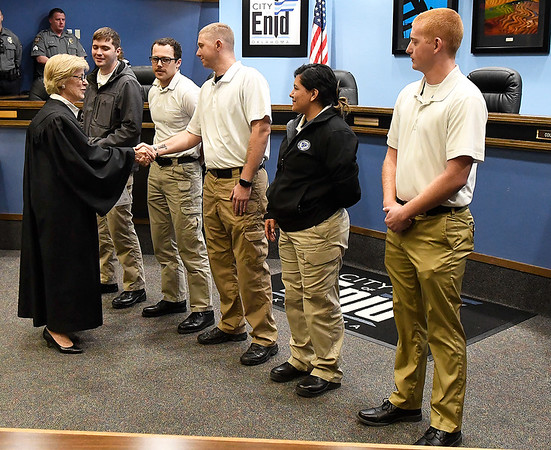 Enid municipal judge, Linda Pickens, shakes hands with the Enid Police Departments,s newest recuits, Sabrina Robledo, Gage Houston, Brian Hatfield, Scott Miller and Jeremy Selvidge, after their swearing in ceremony Thursday, December 5, 2019 at Enid City Hall. (Billy Hefton / Enid News & Eagle)