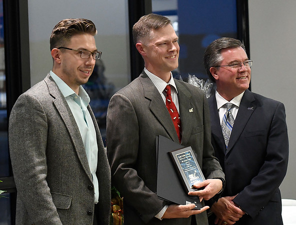 Dr. Aaron Lusby stands between Taylor Venus (left), President Enid Public School Foundation and Dr Darrell Floyd (right), Superintendent Enid Public Schools, after being named the Enid Public Schools Teacher of the Year during an Education Celebration at Prairie View Elementary Wednesday, December 11, 2019. (Billy Hefton / Enid News & Eagle)