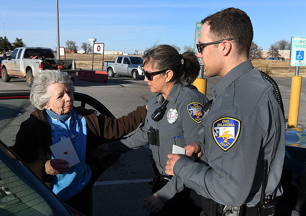 Joan Adkins thanks Enid police officers, Nicole Binckley and Brian Hatfield, after the officers gave her a cash gift Thursday, December 19, 2019 at Jumbo's East. The police department is handing out donated money to random people over the next few days. (Billy Hefton / Enid News & Eagle)