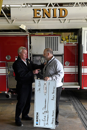 Enid fire chief, Joe Jackson, visits with Shon Jackson of Koch Fertilizer after receiving a donation from the company Tuesday, December 3, 2019. (Billy Hefton / Enid News & Eagle)