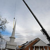 The steeple from Bible Baptist Church is suspended from a crane as roofers replace the shingles on the church Wednesday, December 4, 2019. (Billy Hefton / Enid News & Eagle)