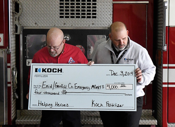 Mike Honigsberg, Director Emergency Management, with Shon Jackson of Koch Fertilizer after receiving a donation from the company Tuesday, December 3, 2019. (Billy Hefton / Enid News & Eagle)