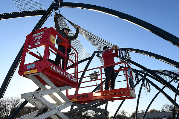 """Volunteers, Marcus Walker and Broderick Williams from Skylar Audio Video, install cable on the downtown art project """"Under Her Wings was the Universe"""" Wednesday, December 18, 2019. (Billy Hefton / Enid News & Eagle)"""