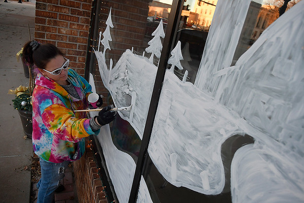 Christy Timberlake paints a holiday scene on a window at Ewbank & Hennigh, PLLC in downtown Enid Tuesday, December 3, 2019. (Billy Hefton / Enid News & Eagle)