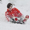 Matthew Tripp kicks up some snow while sledding down the embankment at Garriott and 30th Sunday, December 13, 2020. (Billy Hefton / Enid News & Eagle)