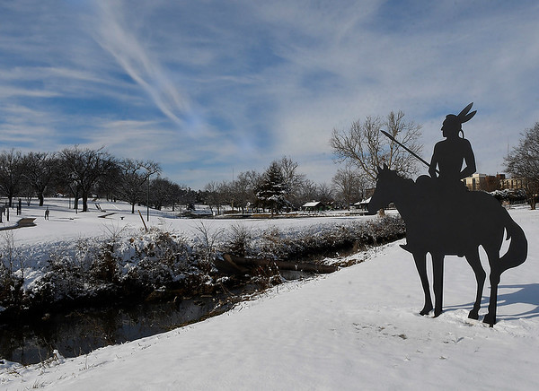 The silhouette of an indian looks over a snow covered Government Springs Park Monday, December 14, 2020. (Billy Hefton / Enid News & Eagle)