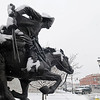 "Snowfall accumulates on H.T. Holden's statue ""Boomer"" as traffic moves east on Maine during a winter storm Wednesday, Feb. 20, 2013. (Staff Photo by BONNIE VCULEK)"